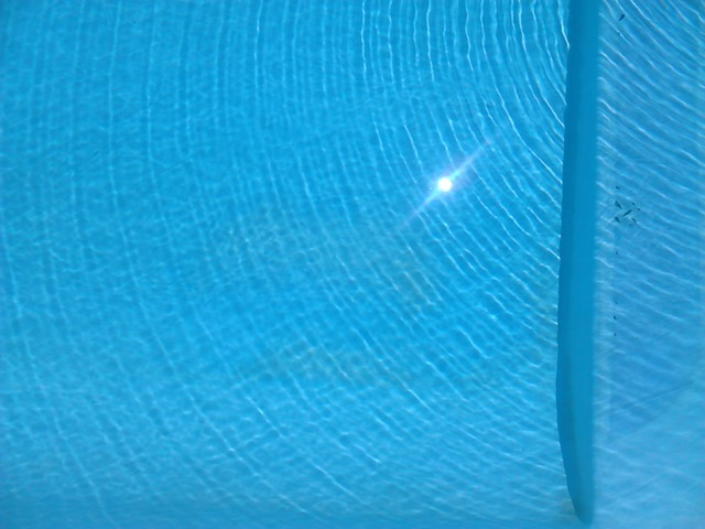 odraz slunce na modré hladině bazénu